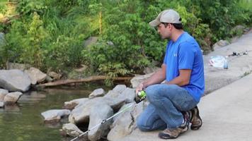 homem pescando na ponte em um riacho, puxando uma vara de pesca