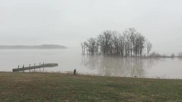 tranquila vista al lago en un día brumoso, con un muelle a la vista