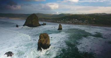 imagens de drone sobre a praia com grandes pedras na água