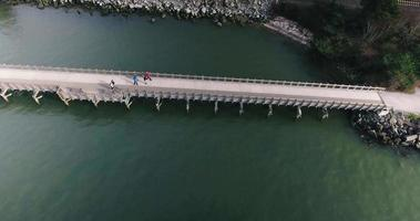 drone descendiendo cerca de un puente sobre peatones video