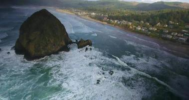 Aerial Drone Shot Panning Out Overlooking Haystack Rock and Town in 4K