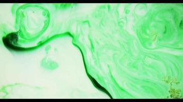 pintura verde moviéndose sobre una superficie blanca creando una textura orgánica de remolinos en 4k