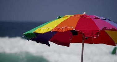 colpo statico di un ombrello colorato con le onde del mare sullo sfondo in 4K