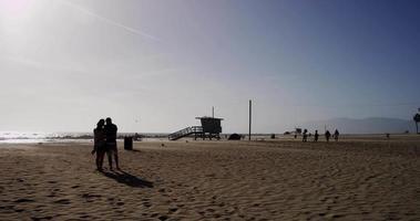 Toma panorámica de gente relajada caminando por la playa en 4k