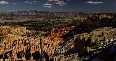 Horizontal panning shot of a red canyon and a valley with trees in 4K