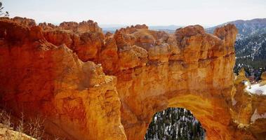 Panoramique horizontal de l'arche de pierre rouge et de la vallée enneigée en 4k