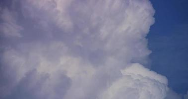 Time lapse of white giant cumulus clouds moving disappearing on blue sky in 4K video