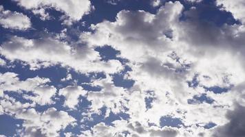 Lapso de tiempo de nubes altocúmulos claras y grises moviéndose en el cielo azul con destellos de luz solar en 4k