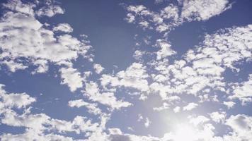Lapso de tiempo de varios grupos de nubes altocúmulos moviéndose en el cielo azul con destellos de luz solar en 4k