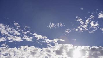 Lapso de tiempo de grandes grupos de nubes altocúmulos moviéndose lentamente en el cielo azul con destellos en 4k video