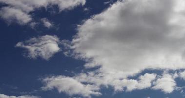 Lapso de tiempo de grandes cúmulos grises alejándose de la cámara en el cielo azul en 4k video