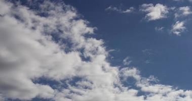 Lapso de tiempo de cúmulos grandes y pequeños alejándose de la cámara en el cielo azul en 4k