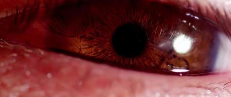 Cerca del ojo humano con iris marrón cambiando el tamaño de la pupila e intentando dormir en 4k