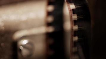 primer plano extremo de un proyector de películas de 8 mm y un detalle de la película que proyecta una sombra en 4k video
