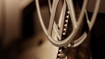 close up de um projetor de filme 8mm, mostrando meio rolo de filme desenrolando o filme em 4k video