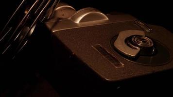 Disposición de dos carretes de película de 8 mm y una cámara clásica girando sobre un fondo oscuro en 4k video