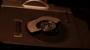Dark scene of an arrangement of two film reels and a classic camera spinning in 4K