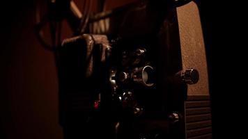 vista de três quartos de um close-up de um projetor de filme de 8 mm funcionando e piscando com bobinas de filme girando em 4k video