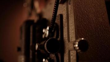 Three quaerter view of a 8mm movie projector working, focus in the lamp flashing in 4K