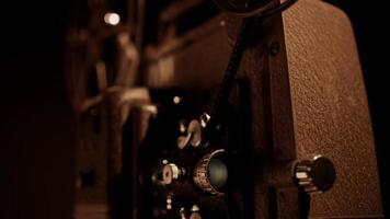 vista de três quartos de um projetor de filme de 8 mm trabalhando e piscando com filme em movimento e bobinas girando em 4k video