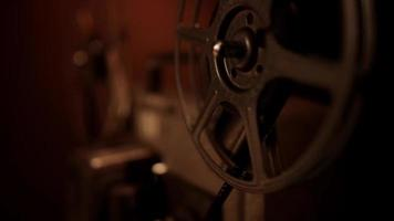 Close up of projector reels spinning, rolling and unrolling the movie film in 4K