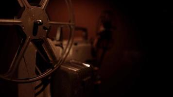 Clip de un proyector de películas de 8 mm trabajando en la oscuridad que solo muestra un carrete de película girando en 4k video
