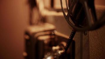 close up de bobina girando e desenrolando filme com luz suspensa em 4k