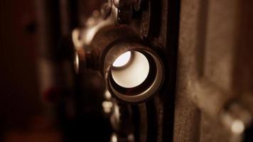 Primer plano extremo de la lámpara y la lente de un proyector de películas vintage con una luz intensa en 4k