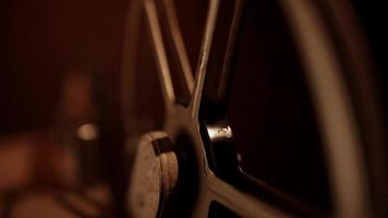Primer plano extremo de la película rodando en carrete oxidado con iluminación cálida en 4k video