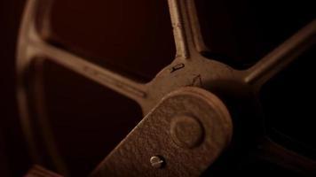 close-up extremo de um rolo de filme enferrujado girando no projetor com iluminação quente em 4k
