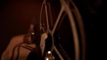 extreme close-up van film rollen en afrollen op roestige spoelen met warme verlichting in 4k