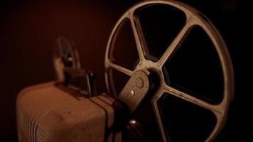 Détail de la vue de trois quarts du projecteur avec des bobines rouillées tournant avec un éclairage chaud en 4k video