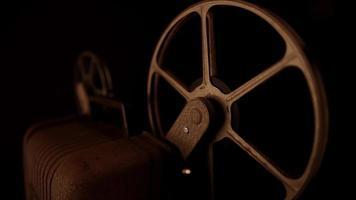 Clip oscuro de vista de tres cuartos del proyector con carretes oxidados girando en 4k