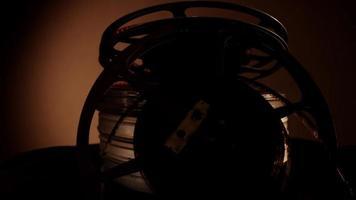 Cerca de la disposición de dos rollos de película antiguos y cuatro latas girando hacia la izquierda con iluminación oscura en 4k