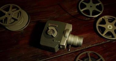 Toma panorámica de varios carretes de película y una cámara antigua sobre una mesa en 4k