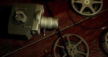 Toma panorámica lenta de tres carretes de película y una cámara antigua sobre una mesa en 4k video