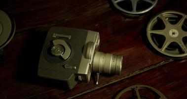 Toma panorámica corta de película volando, cinco carretes y una cámara antigua sobre una mesa en 4k