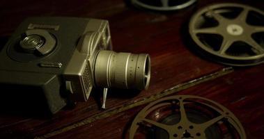 Toma panorámica vertical de rollos de película, cámara vieja y tiras de película cayendo sobre una mesa en 4k