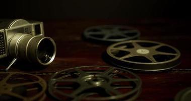 lenta panorâmica de câmera antiga, rolos de filme e uma lata, um rolo caindo na superfície em 4k
