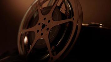 Primer plano extremo de dos rollos de película que giran junto a una cámara clásica que gira con una iluminación cálida en 4k