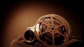 Clip de dos rollos de película girando y una vieja cámara con luz cenital y apariencia de color sepia en 4k