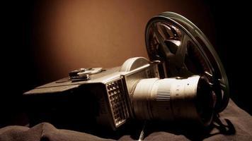 Cerca de dos rollos de película girando y una cámara clásica sobre tela negra con luz cenital en 4k video