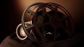 close-up de dois rolos de filme girando ao lado de uma câmera clássica em tecido preto com luz quente no fundo em 4k