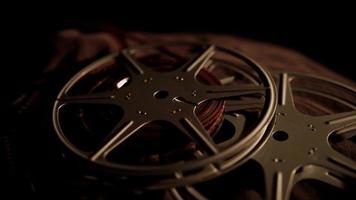 filmrollen die draaien op donkere stof met verlichting aan de rechterkant die harde schaduwen projecteert in 4k