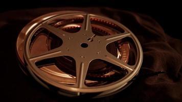 lata de película con carrete en la parte superior girando sobre tela oscura con iluminación superior en 4k