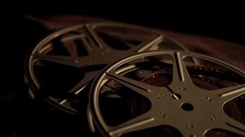 close-up para arranjo de bobinas de filme em fundo preto e iluminação escura girando para a esquerda em 4k video