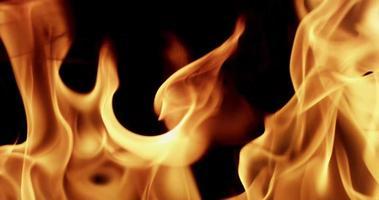Chiuda in su delle fiamme calde con balli su sfondo scuro al rallentatore 4K