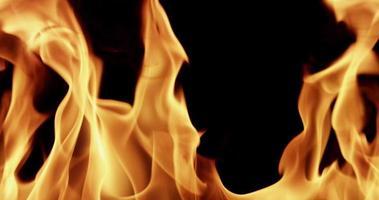 Cerca de llamas de fuego al azar dibujando varias torres sobre fondo oscuro en cámara lenta de 4k