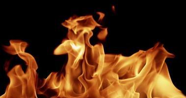 wildes Feuer blinkt auf dunklem Hintergrund für Kriegs- und Gewaltthemen in 4k Zeitlupe