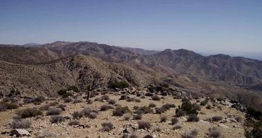 panorâmica indo para a direita da cena desértica com montanhas e arbustos em 4k